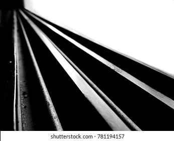 Black and white high contrast image of leading straight lines running diagonally starting broad and then converging far away forming a straight path and with blown out background and dark foreground