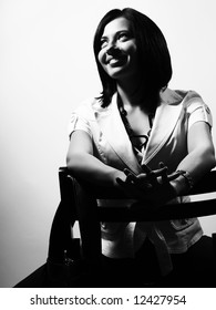 A black and white high-key portrait about a pretty trendy lady with black hair who is sitting on a chair, she is looking up and she is smiling. She is wearing a white coat and a stylish necklace.
