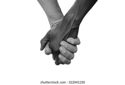 Black and White Hold Hands for Africa Union Peace Love. A beautiful shot with lots of possible background symbols. No to Racism! White woman holds hands with a little native African girl, in Mali.