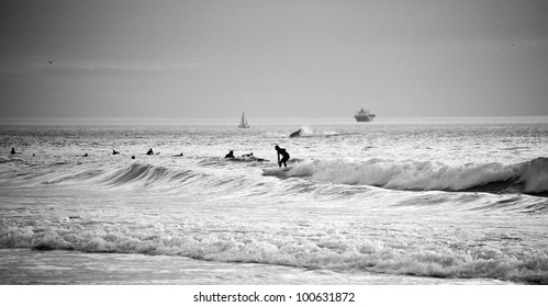Black and white horizontal photo of the surfers in the sea