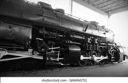 A black and white horizontal view of a four cylinder 2-8-8-2 compound articulated Mallet steam locomotive on display in an outdoor shelter