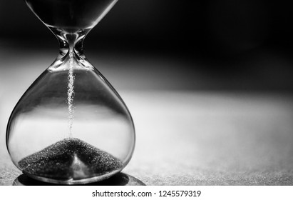 Black and white hourglass with dark background for copy space. Concept for business deadline, urgency and running out of time.