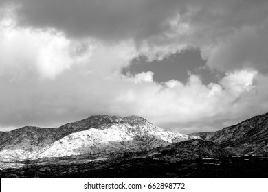 Black and white huge monsoon clouds swooping down over the snow covered Catalina Mountains in winter in Tucson, Arizona