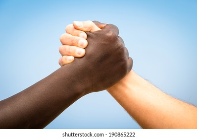 Black and white human hands in a modern handshake to show each other friendship and respect - Arm wrestling against racism