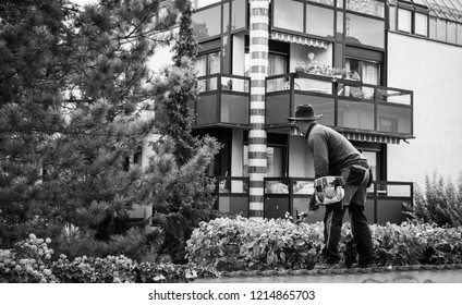 Black and white iamge of unrecognizable gardnere gardener cutting bushes and tree using his electric saws