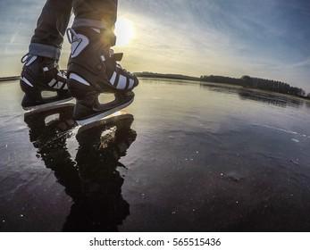 Black and white ice hockey skates, sliding over natural black ice of a Dutch lake at sunrise