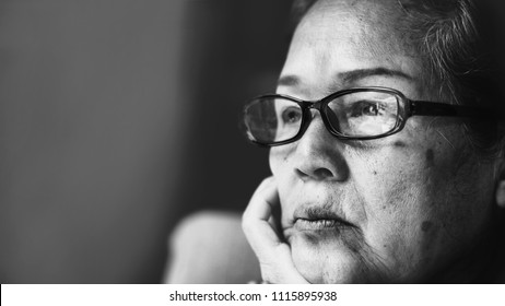 Black and white Image of 60s or 70s  Asian elderly woman wearing eyeglasses rest her chin on her hands .She looking outside or flew away.Sad elderly concept.