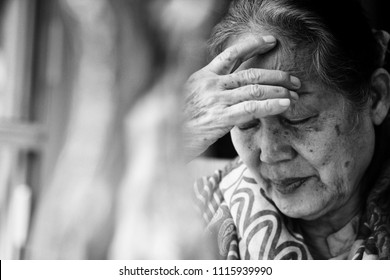 Black and white Image of 60s or 70s  Asian elderly woman facepalm or cover her face by her hands .She may had Headache Symptoms.She looks pain or sick or crying.Sad elderly concept.