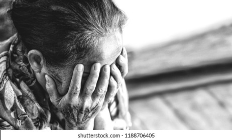 Black and white Image of 60s or 70s  Asian elderly woman facepalm or cover her face by her hands .She may suffering from illness or depress.She looks pain or sick or crying.Sad elderly concept.