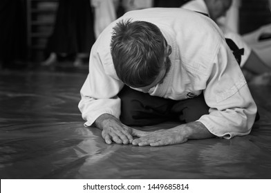 Black and white image of aikido. Athlete in the traditional form of Aikido. White kimano and black hakame. A bow as a sign of respect and welcome.