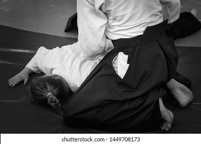 Black and white image of aikido. Athlete girls involved in martial art of Aikido. The traditional form of clothing in Aikido.