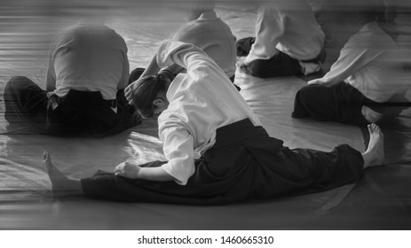 Black and white image of aikido. Àthlete The girl is warming up before training. Gymnastic Twine. The traditional form of clothing in Aikido.