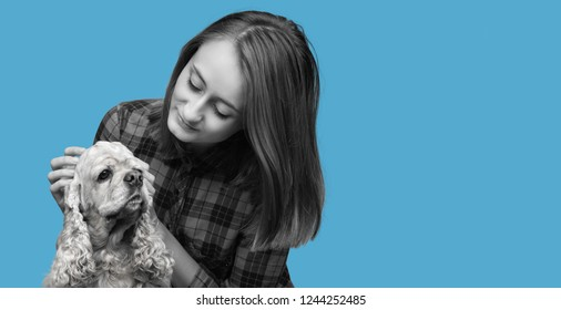 Black and white image of an american cocker spaniel and young beautiful woman on blue background with copy-space