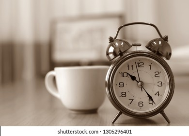 Black and white image, antique alarm clock on the desk coffee cups and computers as the background
