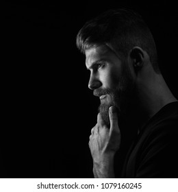 Black and white image of attractive pensive young man looks into the distance stroking his beard over black background