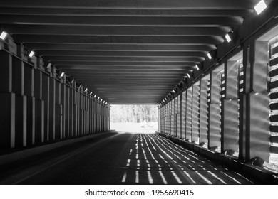 black and white image of avalanche tunnels on the Trans Canada highway through Rogers Pass in  British Columbia shadows cast by sunlight transportation and roads background horizontal format
