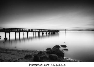 Black and white image: Beach and pier at sunset, Surrey, BC, Canada
