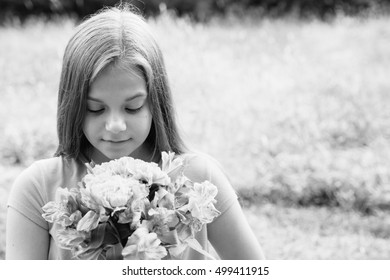 Black and white image of a beautiful girl with flowers and blurred background