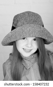 Black and white image of a beautiful smiling little girl in a fashionable hat