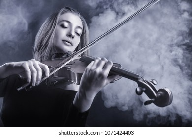Black and white image. Beautiful young woman playing the violin. Fog in the background. Studio shot