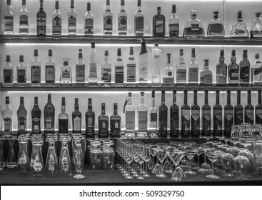 A black and white image of bottles and glassware behind a bar.