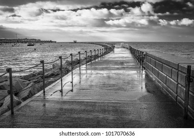 black and white image of the breakwater known as Neptune's Arm in Herne Bay, Kent, UK during a high tide when the wet walkway was closed due to waves breaking over the top of it in the wind.