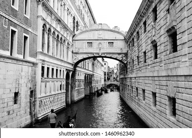 Black and White image of the Bridge of Sighs where prisoners would get their last view of the sun before crossing to the prison. A gondola approaches the bridge on the canal. Venice, Italy