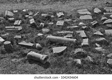A black and white image of broken columns on the ground.