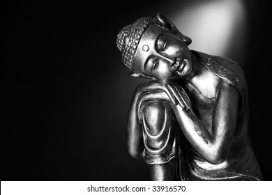 A black and white image of a Buddha statue resting, in front of a dark background with a spotlight.