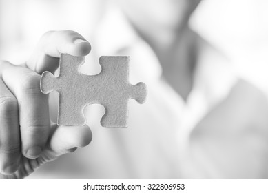 Black and white image of businessman or innovator holding a blank puzzle piece towards you, with copy space ready for your idea, text or sign.