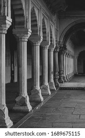 black and white image of carved  pillars with arched passage way of palace