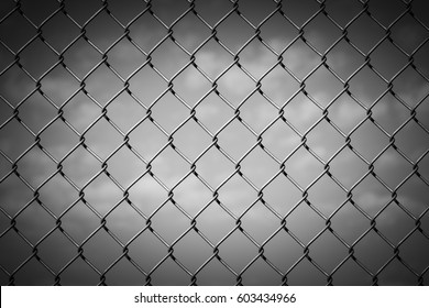 Black and White Image of a Chain Link Fence against a Cloudy Sky with Vignette