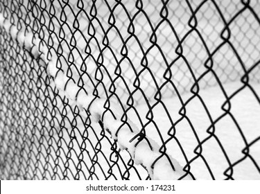 black and white image of a chain linked fence with snow.