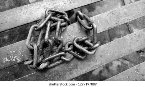 Black and white image of the chains binding of iron, used as a safety on the ship or other construction that requires a strong pull. Ancient chains in use bind  slaves or prisoners