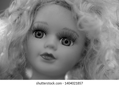 Black and white image of a cheap but pretty collector doll for sale in a thrift store.  Blonde hair, blue eyes, long glamorous lashes, close up.