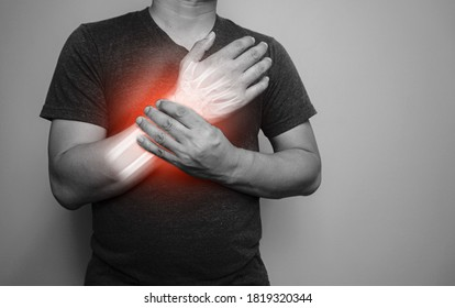 A black and white image Closeup of male arms holding his painful wrist  From arthritis symptoms or Carpal Tunnel Syndrome (CST) Medical healthcare concept.