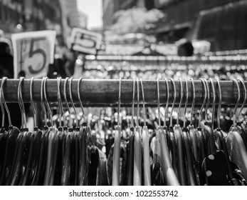 A black and white image of a clothes rail in Petticoat Market, London. The rail is full of coat hangers and has a price tag of £5. Further similar rails blur into the background.