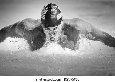 Black and white image of a competitive male participant swimming in a butterfly stroke