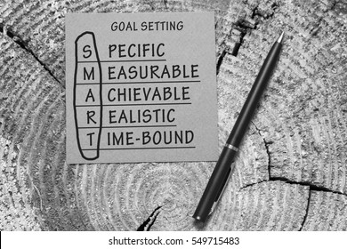 Black and white image of conceptual SMART Goals acronym on piece of wood with pen (Specific, Measurable, Achievable, Realistic, Time-bound)