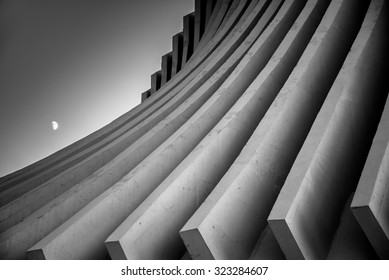 Black and white image of concrete roof beams sweeping down dramatically in curves with the moon rising in a dusk sky.