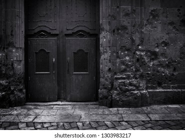 Black and white image dark edition.Shrapnel impact against a wall and ancient temple door Saint Philip Neri in Barcelona Spain