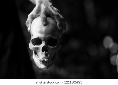 Black and white image of dirty hand of anger or mad man hold dead human skull.Horror background  for Halloween or psycho issue.