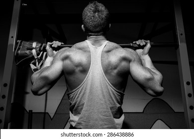 black & white image with dramatic lighting to convey focus, motivated feel. Strong man working out at a gym. The black and white editing adds a feel to the image that does not come across with color.