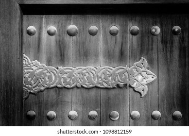 A black and white image of an elaborate metal hinge on the wooden door of a traditional arabian house.