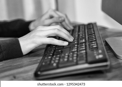 Black and white image of a employee business hands working and typing information data on computer laptop keyboard at wooden table in office. Black and white - monochrome image.