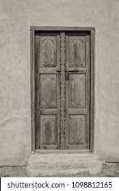 Black and white image of an exterior carved wooden door and step of a restored traditional arabian house.