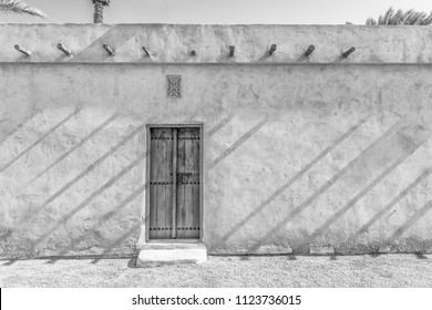 Black and white image of an exterior carved wooden door and step of a restored traditional Arabian house in a wall with sunlight casting diagonal shadows from roof beams.