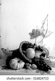 Black and white image of fall cornucopia containing fruits and vegetables and nuts with autumn leaves scattered around with rustic wood background. Vertical composition with copy space in upper left.