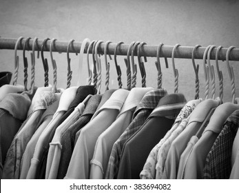 Black and white image of fashion clothes hanging on hanger rack.