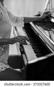 Black and white image of female playing the piano